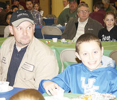 """<div class=""""source""""></div><div class=""""image-desc"""">Brad Forsee and Colton Hayes along with Barry Maddox and Autumn Maddox (background) listen to a speaker at the event.</div><div class=""""buy-pic""""><a href=""""/photo_select/8886"""">Buy this photo</a></div>"""