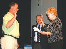 """<div class=""""source"""">Molly Haines</div><div class=""""image-desc"""">Owen County Judge-Executive Carolyn Keith administers the oath of office to Brian Clark during a special meeting of the Owen County Board of Education Thursday while interim Owen County Schools Superintendent Don Martin looks on.</div><div class=""""buy-pic""""><a href=""""/photo_select/1562"""">Buy this photo</a></div>"""