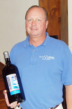 """<div class=""""source""""></div><div class=""""image-desc"""">Curtis Sigretto, holding a bottle of Elk Creek Winery's new Kentucky Speedway wine, was invited to attend the press conference announcing a Sprint Cup race for the Sparta venue. Sigretto was one of several area businesspeople asked to help bring Sprint Cu</div><div class=""""buy-pic""""><a href=""""/photo_select/1070"""">Buy this photo</a></div>"""