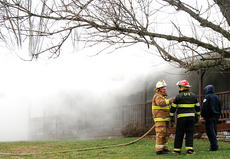 "<div class=""source"">Molly Haines</div><div class=""image-desc"">New Liberty Fire Chief Greg Davis discusses the next step of action with a fellow firefighter Thursday as smoke rolls from the attic of a mobile home on Hwy. 355, located next to Frankie and Johnny's restaurant.