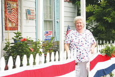 """<div class=""""source"""">Photo by Molly Haines </div><div class=""""image-desc"""">It may seem like every day is the Fourth of July at the home of local dentist Joy Arnold-Morse. She has adorned much of her home and surroundings with red, white and blue to honor our country. </div><div class=""""buy-pic""""><a href=""""/photo_select/9925"""">Buy this photo</a></div>"""