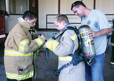 """<div class=""""source""""></div><div class=""""image-desc"""">Cameron Duvall and Christopher Curtis assist one another in getting the proper firefighting equipment on, while Jonesville Volunteer Fire Department Chief Chase Duvall looks on.</div><div class=""""buy-pic""""><a href=""""/photo_select/5703"""">Buy this photo</a></div>"""