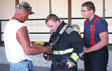 """<div class=""""source""""></div><div class=""""image-desc"""">Owen County Fire Department Volunteer Firefighter Greg Estes helps Daniel Lilly with his equipment, while Erik Lilly also helps out. </div><div class=""""buy-pic""""><a href=""""/photo_select/5702"""">Buy this photo</a></div>"""
