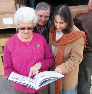 : Owen County Historical Society President Jeannie Baker, left, and members Larry Dale Perry and Bonnie Strassell look over one of the first copies of the Owen County Family History Book