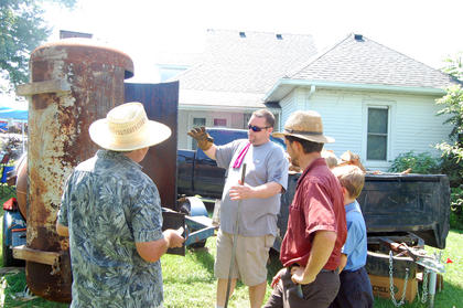 John Howard talks with some of the 127 yard sale shoppers and shows off the barbecue smoker. Howard and his cousin Willie Hopkins built the smoker for their business Double H Bar-B-Q.