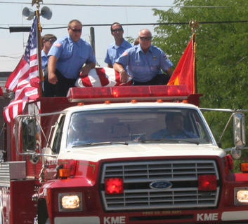 Firefighters accompany the body of Walker T. Ellis atop a fire truck to the Owenton Cemetery. Ellis, one of the founding members of the Owenton/Owen County Fire Department, passed away July 1.