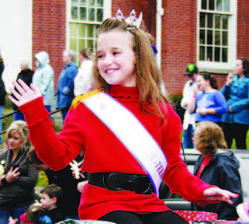 The 2012 Owen County 4-H Fair and Horse Show Miss Pre-Teen Chelsea Lathrem waves to the crowd during her ride in the parade.