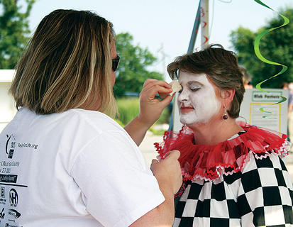 Vanessa Humphries helps Karen Wotier apply makeup.