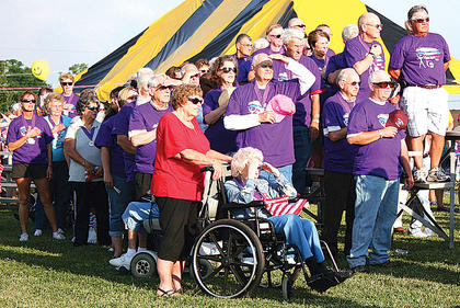 The 2012 Relay for Life cancer survivors salute the flag as the Star Spangled Banner is sung. 