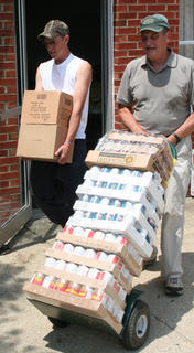 Simon Peters, left, and Jim Morgan carry supplies out to a pallet which will be loaded on the truck.