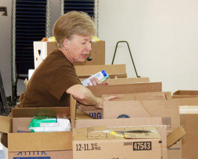 Anna Cook, one of the organizers, helps load supplies into boxes for delivery.