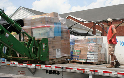 Kelly Wainscott directs another load of supplies onto the back of Danny Cook's tractor-trailer.