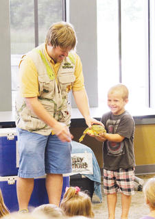 "Luke Dial, 6, holds the squishy bullfrog during his time on the ""Silly Safari."""