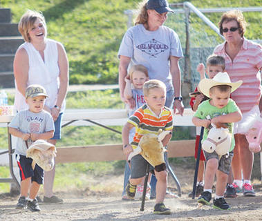 Contestants in the stick horse race during Family Fun Night take off as friends and family look on.