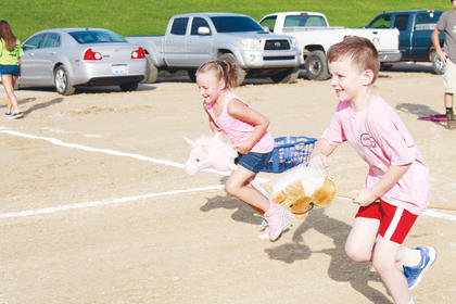 Cloee O'Banion, 6, and Isaiah Collins, 6, compete in the stick horse race.