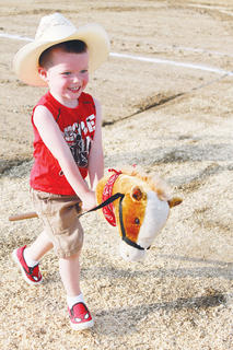 Braxton Perkins, 2, participates in the stick horse race.
