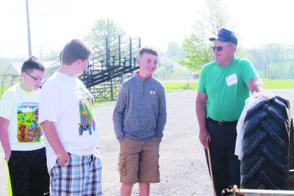 Red Shryock, right, talks tractor safety with Landen Perkins.