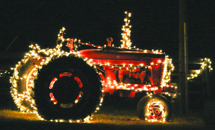 A tractor lit up by Christmas lights on the farm of Brian and Margaret Forsee.