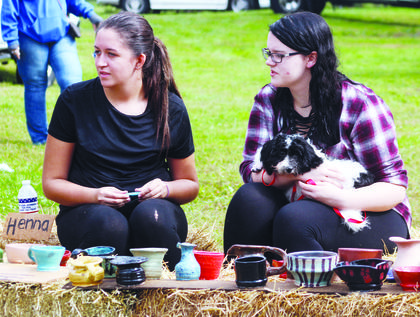 Jessica Hardin, Lydia Hobbs and dog Gus watch as a variety of festivities take place.