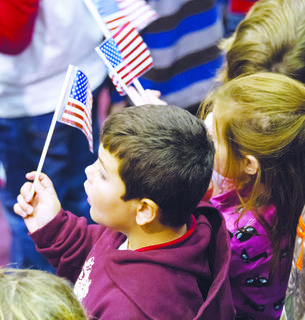 Students wave flags during the celebration.