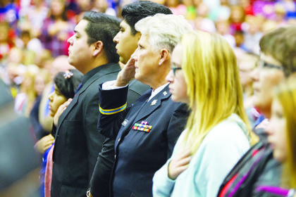 Debbie Primeau, second from right, salutes during the Veterans Day celebration held at Owen County High School Nov. 11. The celebration brought together all district students and honored veterans in attendance with song, speeches, band performances, as well as a catered lunch.