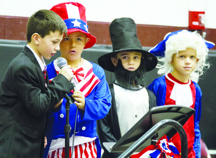 Quinton Miller as John F. Kennedy, Christian Dempsey as Uncle Sam, Harper Duvall as Abraham Lincoln, and Bryson Tirey as George Washington, recite the Pledge of Allegiance.