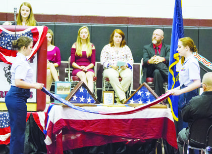 Savannah Hubbuch and Emma Ashcraft, members of the Civil Air Patrol, perform a flag folding demonstration. Above: Students wave flags during the celebration.