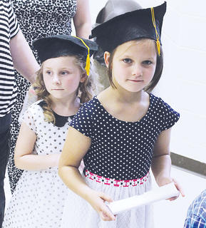 Maylee Bastin (left) and Brooklyn Elliot (right) make their way out of the gymnasium following their graduation.