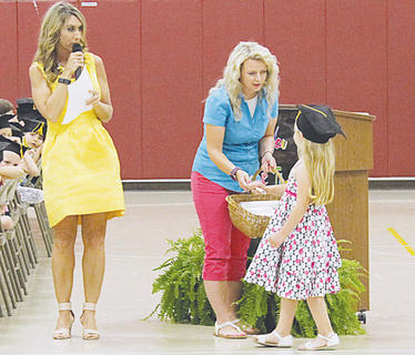 Lexie Chappell, from Jan Blackwell's class, receives her Kindergarten diploma from Kristal New.