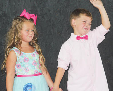 Contestants Abigayle Dempsey and Carson Carter greet the crowd that gathered July 14 for the Little Miss and Mister pageant.