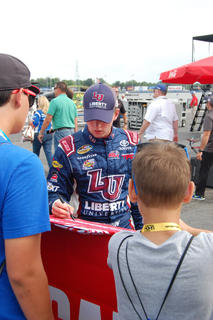 William Byron signs autographs after qualifying his truck Thursday.