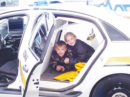 Bentley and Zoey Bond pose for a photo in the back of an Owen County Sheriff's Department cruiser.