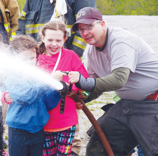 Maddy Hudnall and Mallory Groves take a turn testing the fire hose with Owen County Fire Chief Robb Chaney.