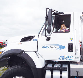Lockett Beckham waves from the driver's seat of an Owen Electric truck.