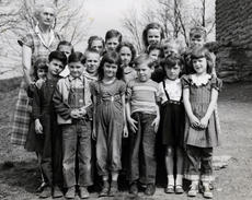 "<div class=""source""></div><div class=""image-desc"">New Columbus Grade School, first and second grades, 1952-53.  Front row:  Wayne Wright,  Dorothy Clifton, George Aubrey,  Lynette Carr, Nita Ann True.  Second row:  Dennis Jones, Eddie Dempsey, Doris Ann Hammond, Lucille Wright, Carolyn Hunter, Hazel Jenkins (partially hidden).  Back row:  Mary Aubrey, Judy Parr, Ruby Parr, Joe Virgil Jones, Betty Clifton, Georgia Green.  The teacher is Miz Zell (Ozella) Jackson True. She is uncharacteristically NOT smiling in this photograph. </div><div class=""buy-pic""></div>"