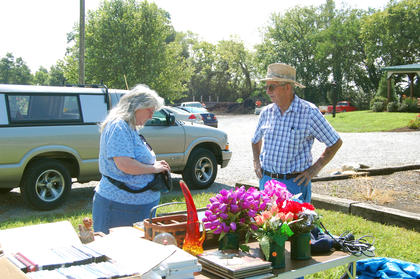 Don Wainscott talks with Diana Arnold, from Sadieville. Wainscott was selling his own items as well as items for the New Liberty Baptist Church.