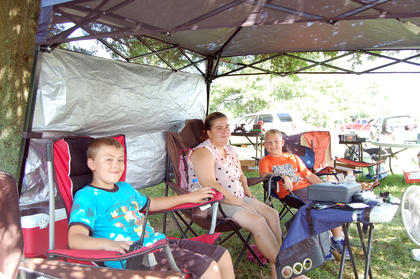 Connor Lunsford, 9, Jennifer Alexander and Corey Elliott, 9, try to keep cool under a canopy while set up at the Lighthouse Church.