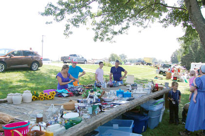 Shoppers browse through items set up in front of Carla Combs' house.