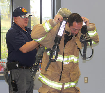 Assistant Owenton Fire Chief David Lilly assists Canchola with his bunker gear during a demonstration.
