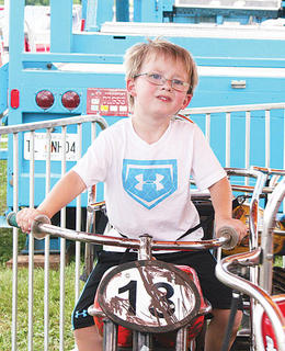Mason Bass, 4, cools off on a midway ride.
