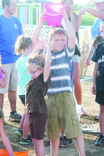 Clayton Stewart gets a little help from Bailey Stewart during the water-bucket relay during Family Fun Night.