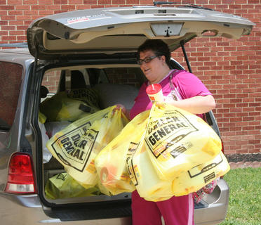 Kitty Cammack carries armloads of needed supplies from her van to the First Baptist Church Fellowship Hall.