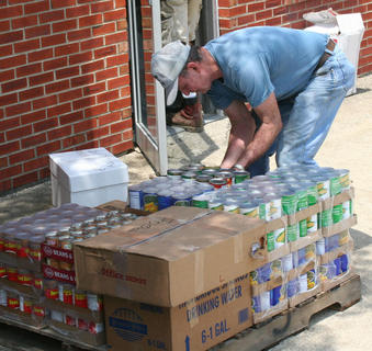 Jerry Wainscott places canned food on pallets for distribution in Alabama.
