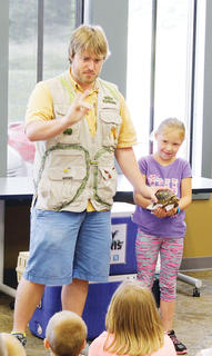 "Stella Wilson, 6, gets to hold a turtle during a demonstration at the Owen County Public Library's presentation of the ""Silly Safari"" animals."