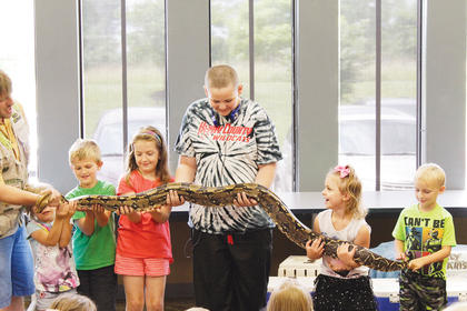 Haley Combs, 8, Dru Gentry, 12, Harmony Sams, 4, and Ezekiel Mefford team up to hold the large boa constrictor during the show.
