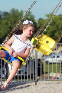 Brenna Miller, 5, enjoys a ride on the swings Thursday at the Owen County 4-H Fair and Horse Show.