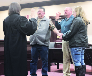 Bob Risch, left, and Brian Riddle, center, take the oath of office for the third and second-district constable's seats, respectively. Riddle's daughter, Emily Riddle, holds the Bible used during the ceremony.