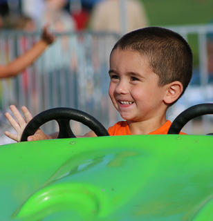 Easton Wagers, 3, waves to his family from one of the carnival's rides. Despite rains Friday and Saturday, this year's annual county fair saw mostly decent weather for the week's activities.