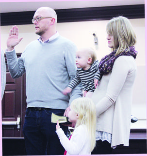 Newly elected fourth-district magistrate Chad Rose takes the oath of office accompanied by his wife Anna Rose and their children.