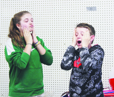 Sixth-grade students Gracie Newby and Bryce Thornton demonstrate applying the proper amount of sunscreen at the sun safety station.